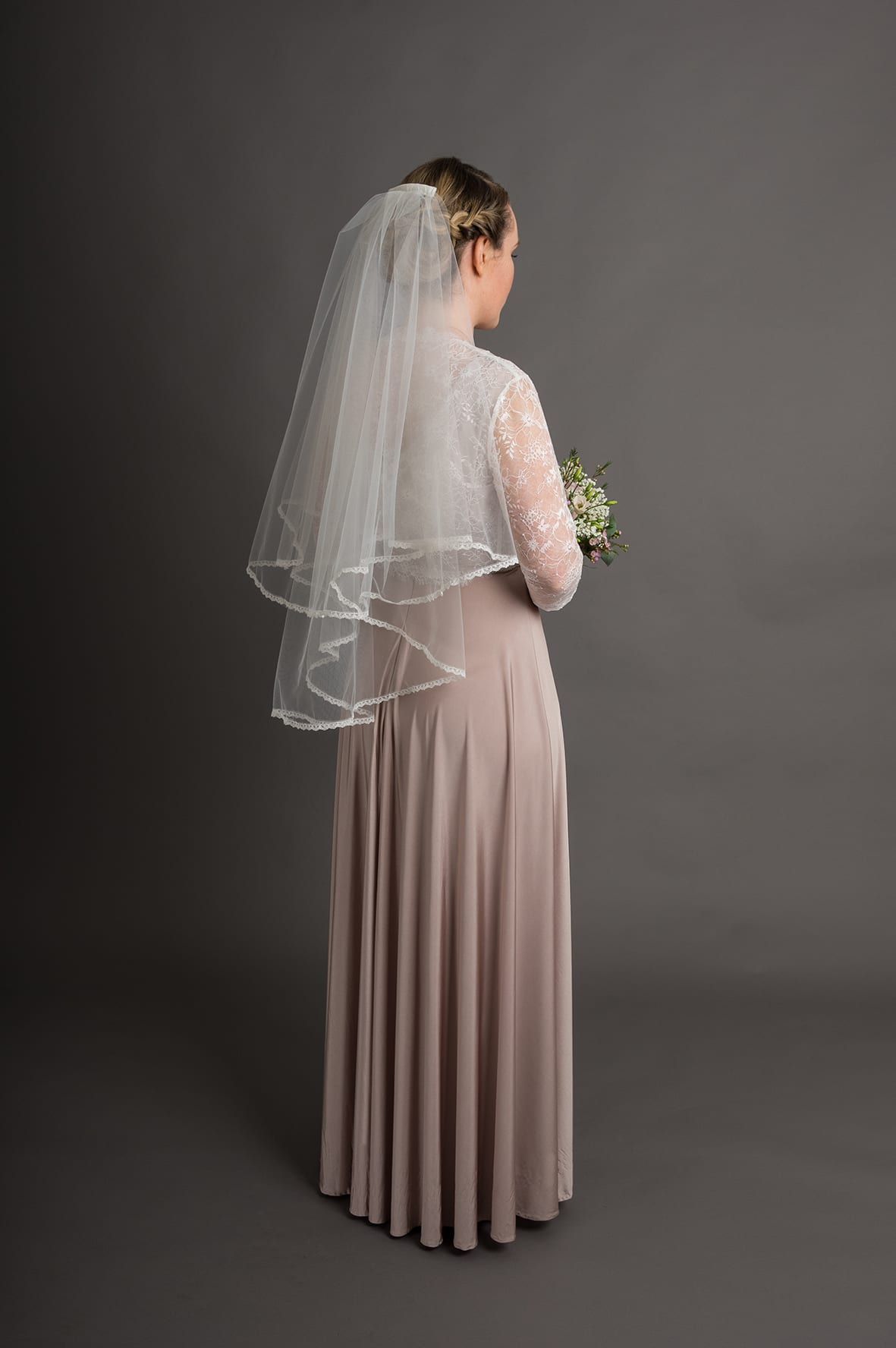 Model wears the Wentworth Veil, waist length in medium ivory with the combed lace header. Paired with the Kensington Jacket, ¾ length sleeve version.